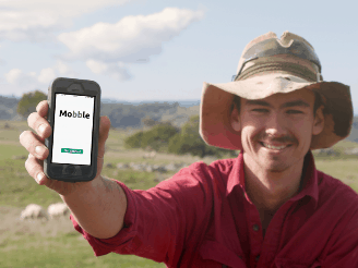 A farmer holding a phone with the Mobble app on it