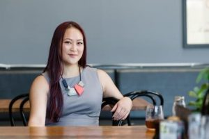 Jeanette Cheah from Hex sitting at a cafe table looking at the camera